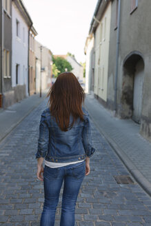 Rear view of brunette woman in a street - HCF000048