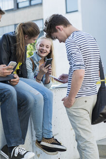 Group of friends outdoors using cell phones - UUF001367