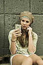 Teenage girl with cell phone at concrete wall - UUF001395