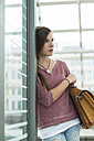 Teenage girl with bag at commuter train station - UUF001428