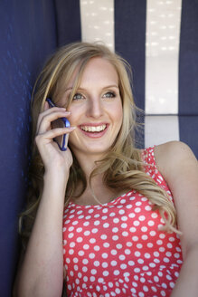 Portrait of smiling young woman telephoning with smartphone - GDF000363