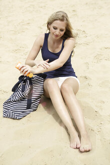Smiling young woman sitting on the beach using suncream - GDF000364