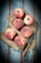 Six doughnut peaches, Prunus persica var. platycarpa, and a knife on cloth and wooden table - MAEF008809