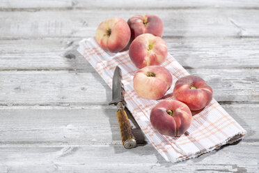 Six doughnut peaches, Prunus persica var. platycarpa, and a knife on cloth and  wooden table - MAEF008813
