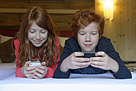 Portrait of brother and sister lying on bed using their smartphones - LBF000835