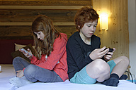 Brother and sister sitting on bed with their smartphones - LBF000868