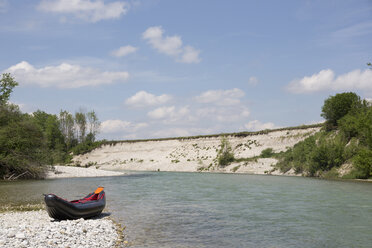 Germany, Bavaria, little rafting boat lying on rocky beach at waterside of Isar River - TKF000373