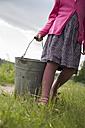 Germany, Schleswig-Holstein, little girl carrying a zinc bucket on a meadow - TKF000374