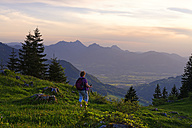 Germany, Bavaria, Upper Bavaria, Chiemgau Alps, Samerberg, Hochries area near Grainbach, Hiker in the evening light - LB000826