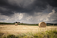 Italy, Tuscany, Chianti, Tuscan landscape with haybales at upcoming thunderstorm - SBDF001036