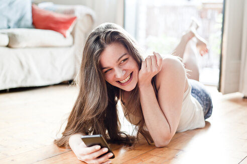 Portrait of smiling young woman with  smartphone at her living room - FEXF000155
