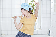 Portrait of young woman singing in the bathroom using massage brush as microphone - FEXF000170