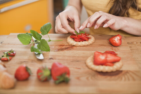 Young woman garnishing pies with strawberries and mint, partial view - FEXF000179