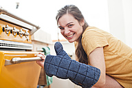 Portrait of smiling young woman in front of her oven - FEXF000184