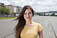 Germany, North Rhine-Westphalia, Cologne, portrait of smiling young woman - FEXF000203