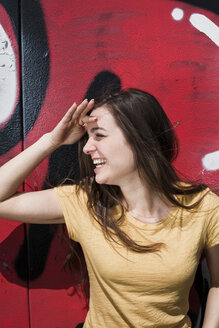 Portrait of smiling young woman standing in front of a graffiti - FEXF000206