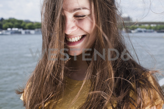 Germany, Cologne, portrait of smiling young woman with blowing hair standing in front of Rhine River - FEXF000216