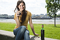 Germany, Cologne, portrait of smiling young woman sitting in front of Rhine River drinking red wine - FEXF000224
