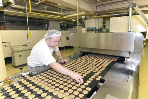 Germany, Saxony-Anhalt, man controlling cookies  in a baking factory - LYF000262