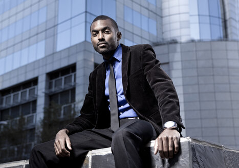 Southafrica, young African business man  wearing black suit sitting in front of an office building - KD000001