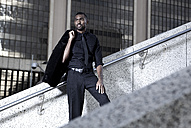 Southafrica, young African business man standing on a staircase - KD000004