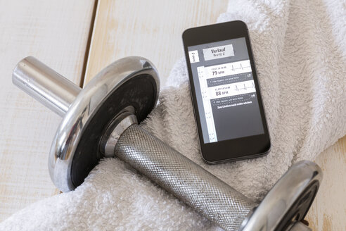 Smartphone showing heart rate monitor, towel, tablets and dumbell on wood - DRF000994