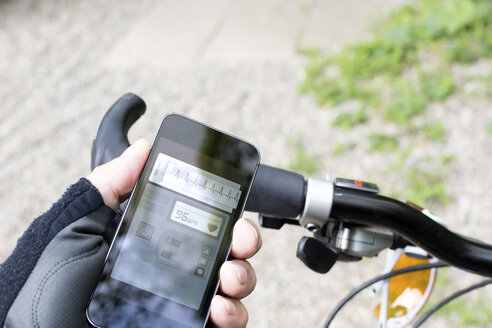 Hand of mountain biker holding smartphone with heart rate monitor - DR000996