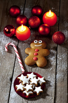 Gingerbread man, sugar cane, plate of cinnamon stars, Christmas baubles and lighted candles on grey wood - CSF021984