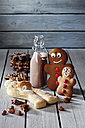 Two gingerbread men, bottle of cocoa, Stutenkerl and Christmas cookies on grey wood - CSF021999