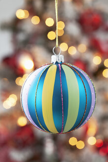 Christmas bauble hanging in front of blurred flares - CSF022032