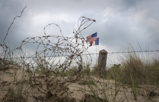 France, Lower Normandy, Manche, Sainte Marie du Mont, Utah Beach, Barbed wire fence and French and US flag - MKFF000047