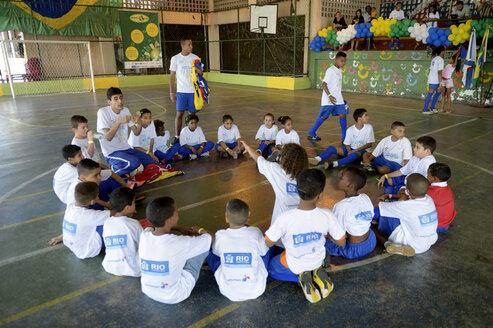 Brazil, Rio de Janeiro, Favela Morro dos Prazeres, soccer coach talking to children - FLK000386