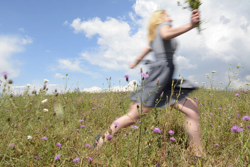 Young woman running on wildflower meadow - BFRF000476