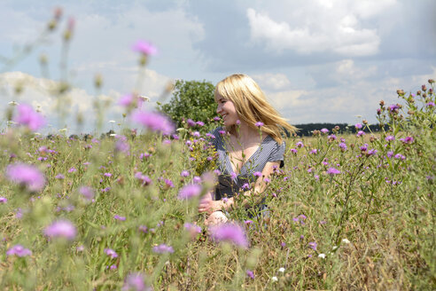 Happy young woman in wildflower meadow - BFRF000477