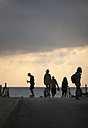 France, Aquitaine, Seignosse, silhouettes of people in front of the sky at twilight - FA000031