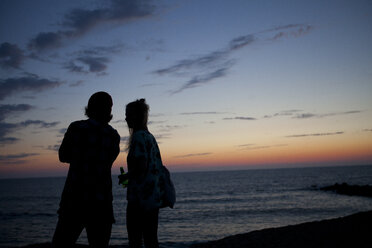 France, Aquitaine, silhouette of couple watching the sea at twilight - FAF000036