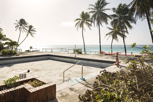 Caribbean, Antilles, Lesser Antilles, Barbados, abandoned hotel, mid adult woman sitting by the empty pool - SK001582