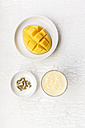 Sliced mango, cardamom capsules and a glass of mango lassi on white ground - EVGF000747