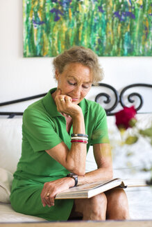 Portrait of senior woman reading book on a couch - FX000042
