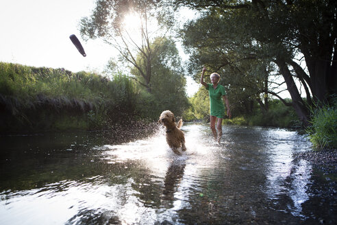 Senior woman playing with her dog in water - FX000047