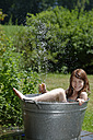 Girl holding garden hose while bathing in a zinc tub - LBF000881