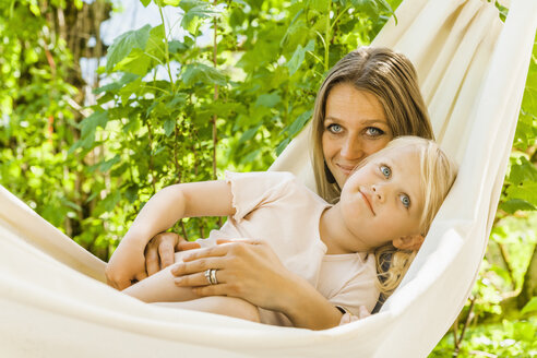 Mother and daughter relaxing in hammock - TCF004161