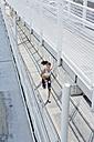 Germany, Munich, Female jogger running on a bridge - MAEF008868