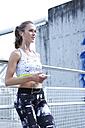 Germany, Munich, Female jogger listening music - MAEF008900