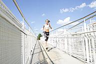 Germany, Munich, Female jogger running on a bridge - MAEF008871
