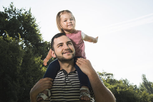 Father carrying little daughter on his shoulders - UUF001517