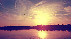 Germany, North Rhine-Westphalia, Minden, balloons over lake at sunset - HOHF000920
