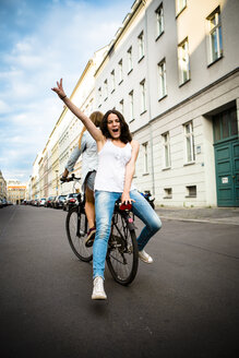 Germany, Berlin, two female friends driving on a bicycle - FX000054