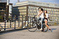 Germany, Berlin, two female friends driving on a bicycle - FX000058