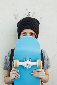 Portrait of young female skate boarder holding hiding behind her skateboard - EBSF000283